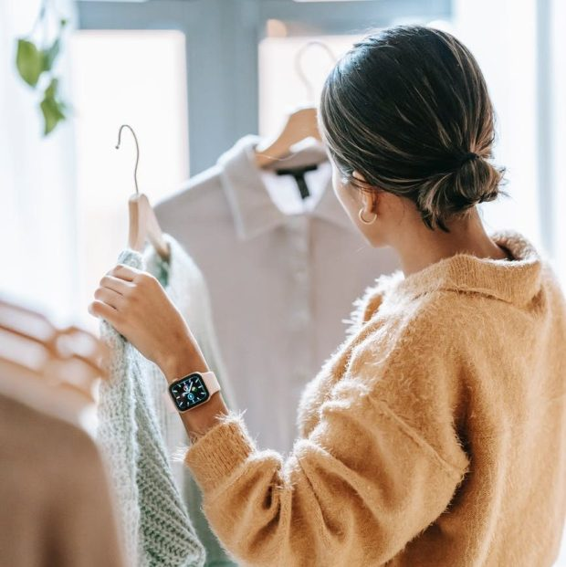 woman choosing outfit in store, sustainable fashion entails taking the time to look at labels and materials