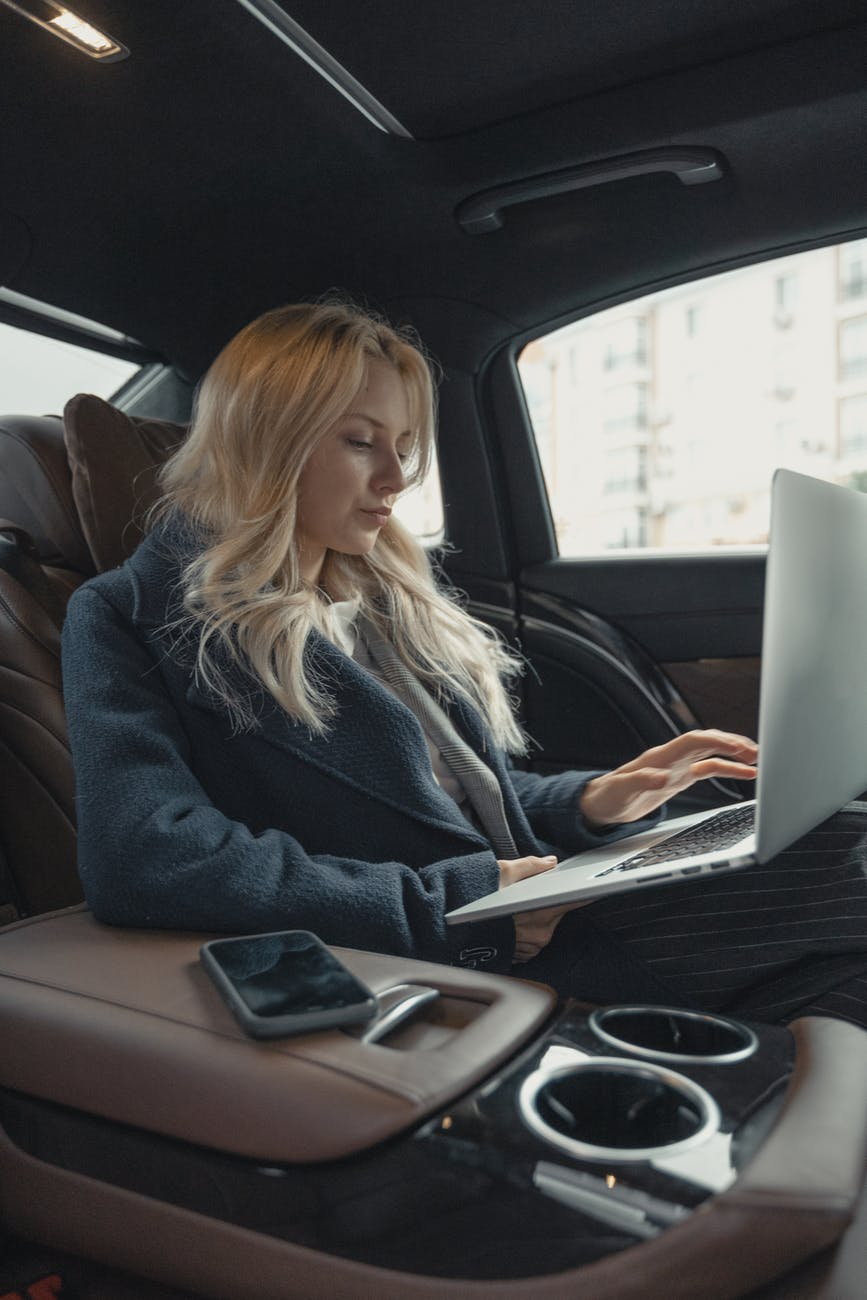 woman in gray business suit sitting at the back seat of a luxurious car