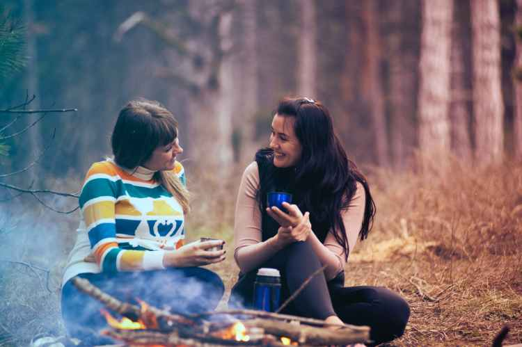 two women sitting on ground near bonfire