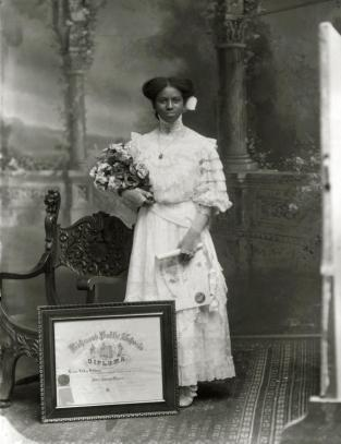 """Photograph, """" Leonie Helen Holmes,"""" 1909. In this photograph, Leonie Helen Holmes holds a diploma while a second, framed diploma sits at her feet. The diploma on the floor is her diploma from Richmond Colored Normal and High School; the one in her hand is probably a diploma from a six- to eight-week summer """"normal""""—a special program designed to train teachers. Summer normals were instituted around 1906 as part of the state's efforts to reform public schools by establishing standards for teachers. (VHS accession number: 2003.298.29 a)"""