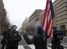 """A protester, carrying an upside down American flag, and sporting a peace sign, asks police """"is your paycheck worth this?"""" Photo by Vaishnavee Sharma/BU News Service."""