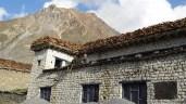 Zwei Maenner auf einem Hausdach in Muktinath. Eine Menge Holz auf dem Dach ist in Mustang ein Statussymbol