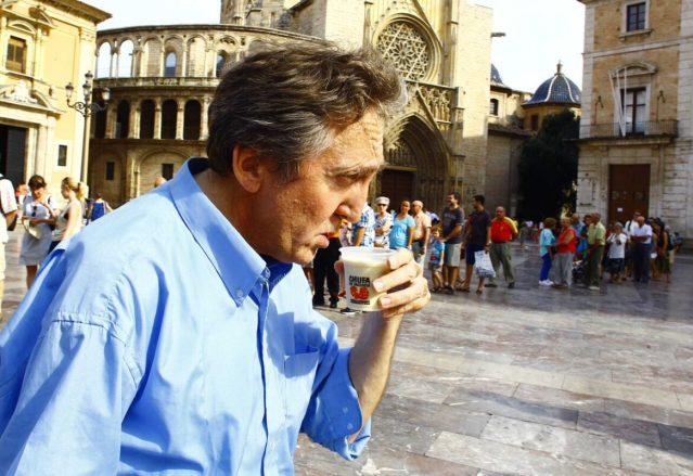 Un hombre toma un vaso de horchata en la plaza de la Virgen