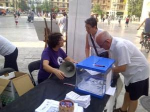Una directiva explica la campaña a dos personas que se acercaron a la mesa de la plaza de la Virgen el pasado sábado/vlcciudad