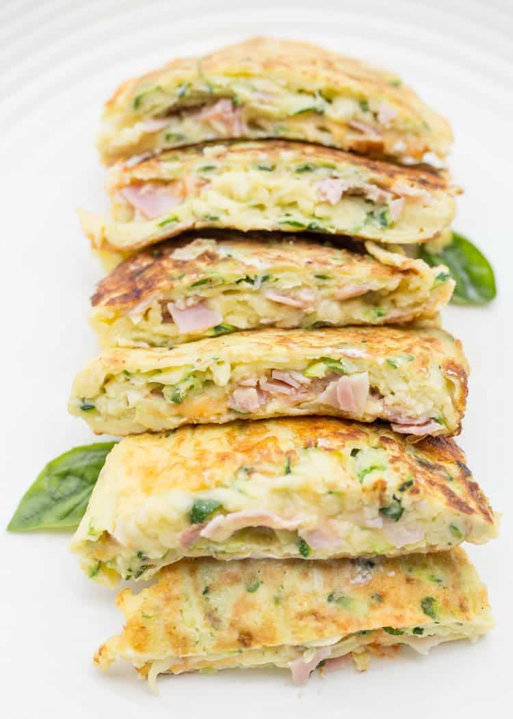 Breakfast egg zucchini fritters i stacked on top of each other, cut in halves. Stuffed with ham and cheese.