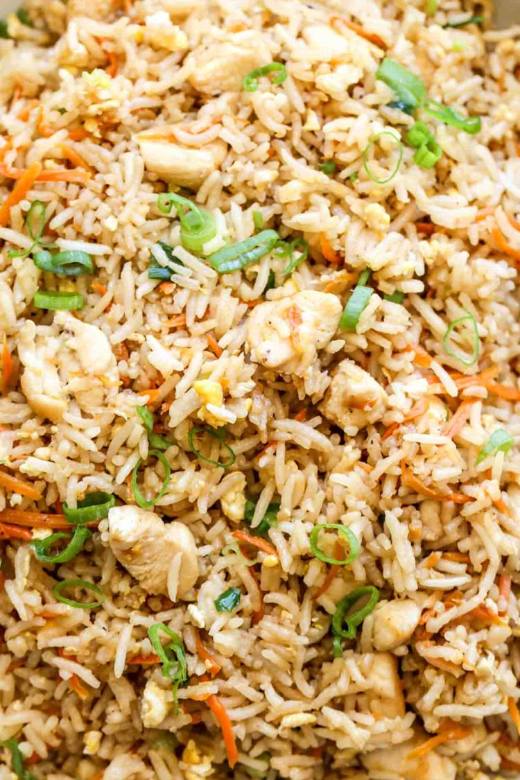 Simple chicken fried rice recipe with rice, chicken, eggs, carrots, and green onions.