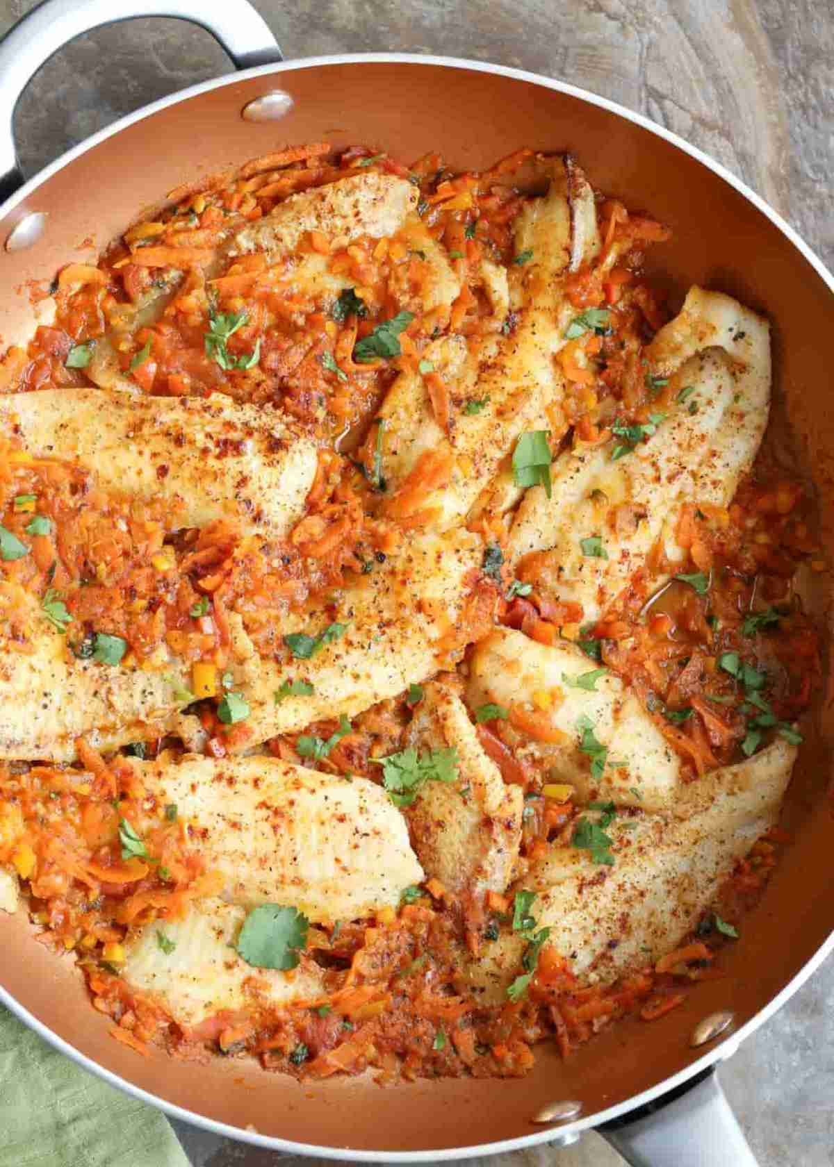 Flounder fish with vegetables recipe in a skillet.