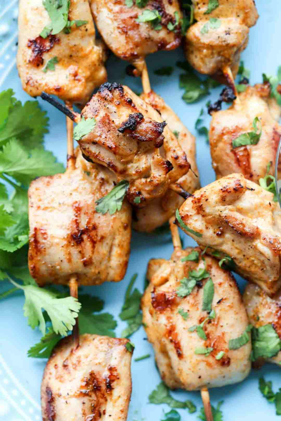 A close up of Grilled Buffalo Ranch Chicken on skewers, topped with fresh cilantro.