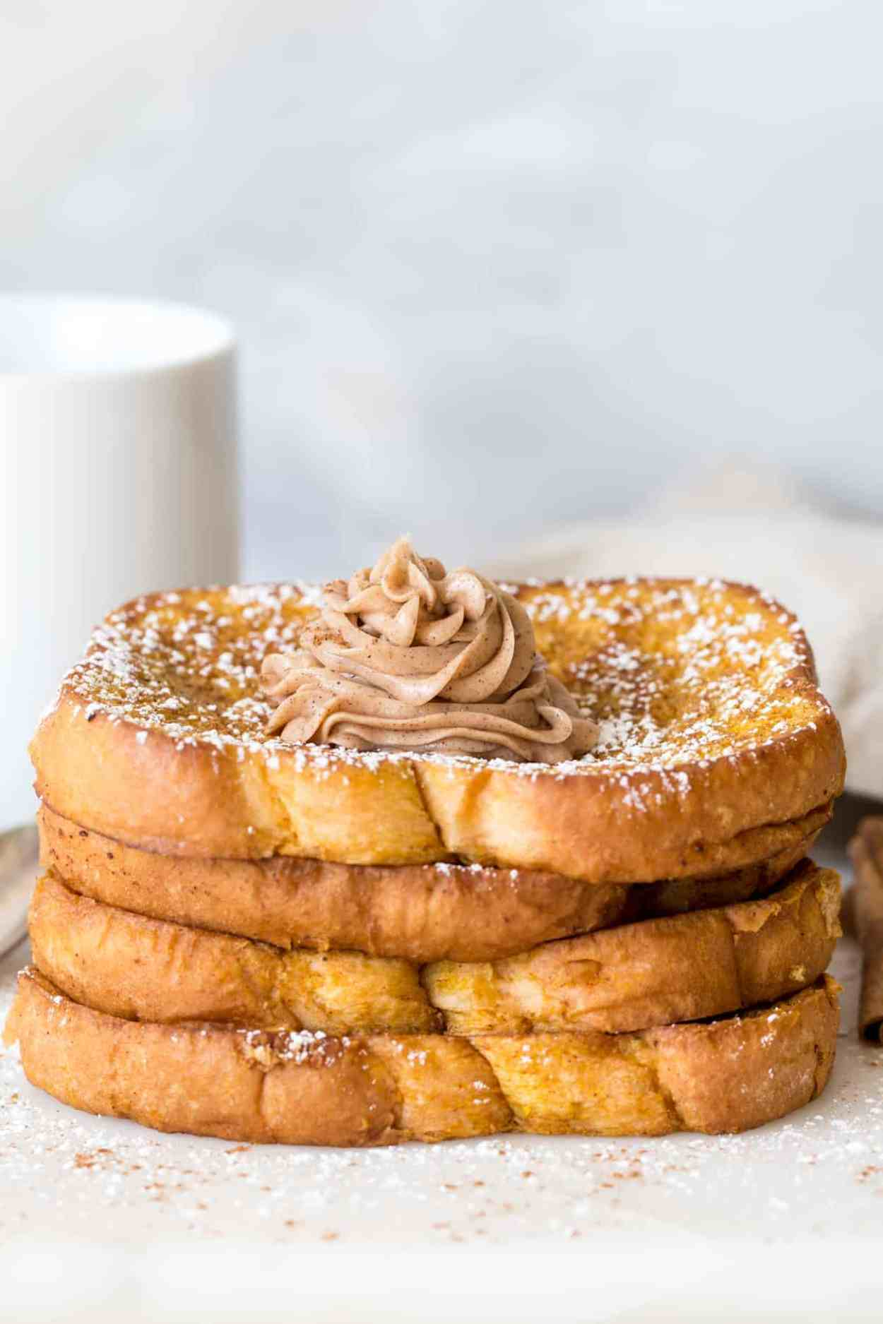 Easy french toast recipe with pumpkin stacked on top of each other topped with powdered sugar, cinnamon, and pumpkin butter.