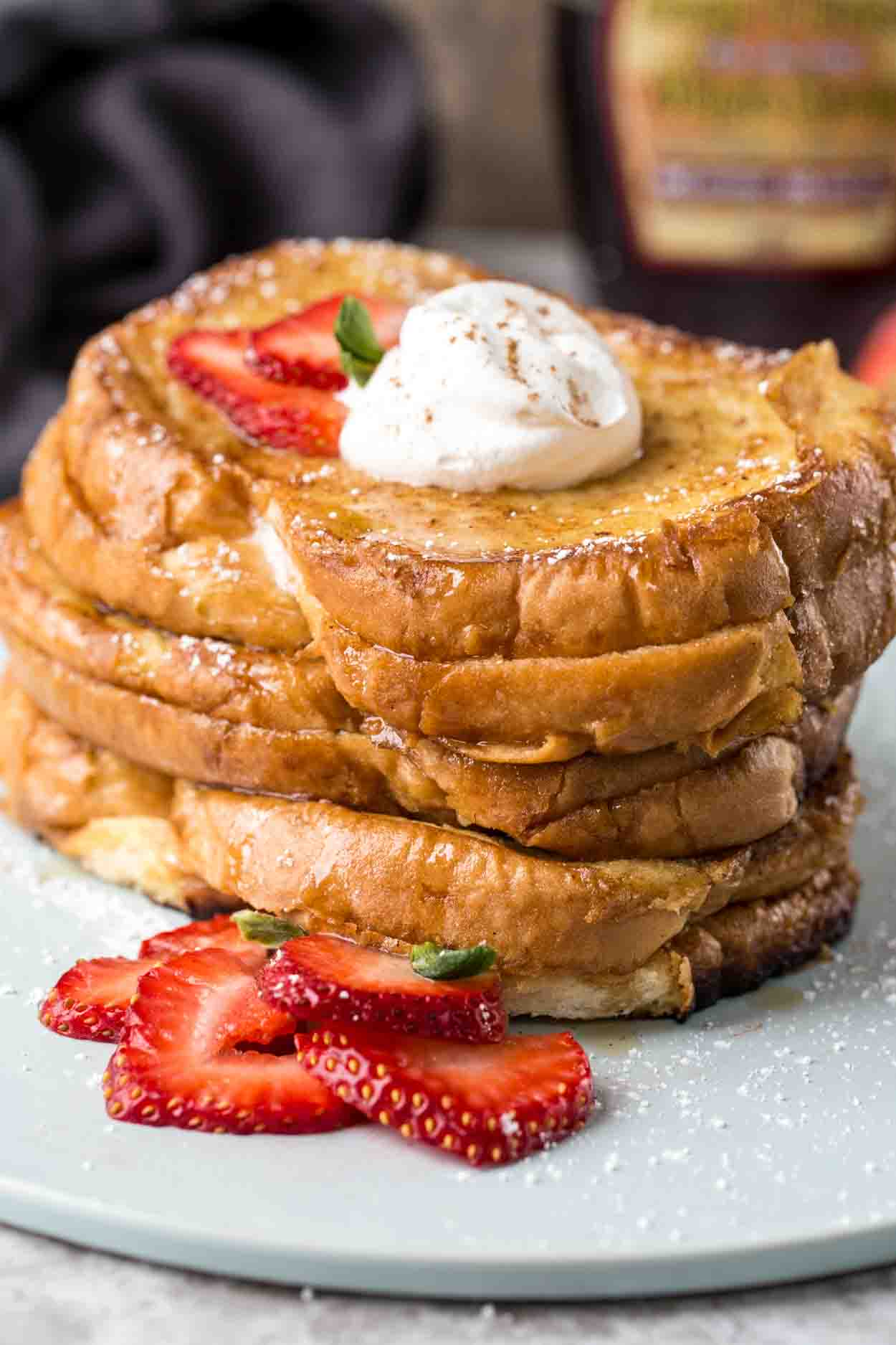 Strawberry cheesecake stuffed french toast recipe, topped with whipped cream and fresh strawberries.