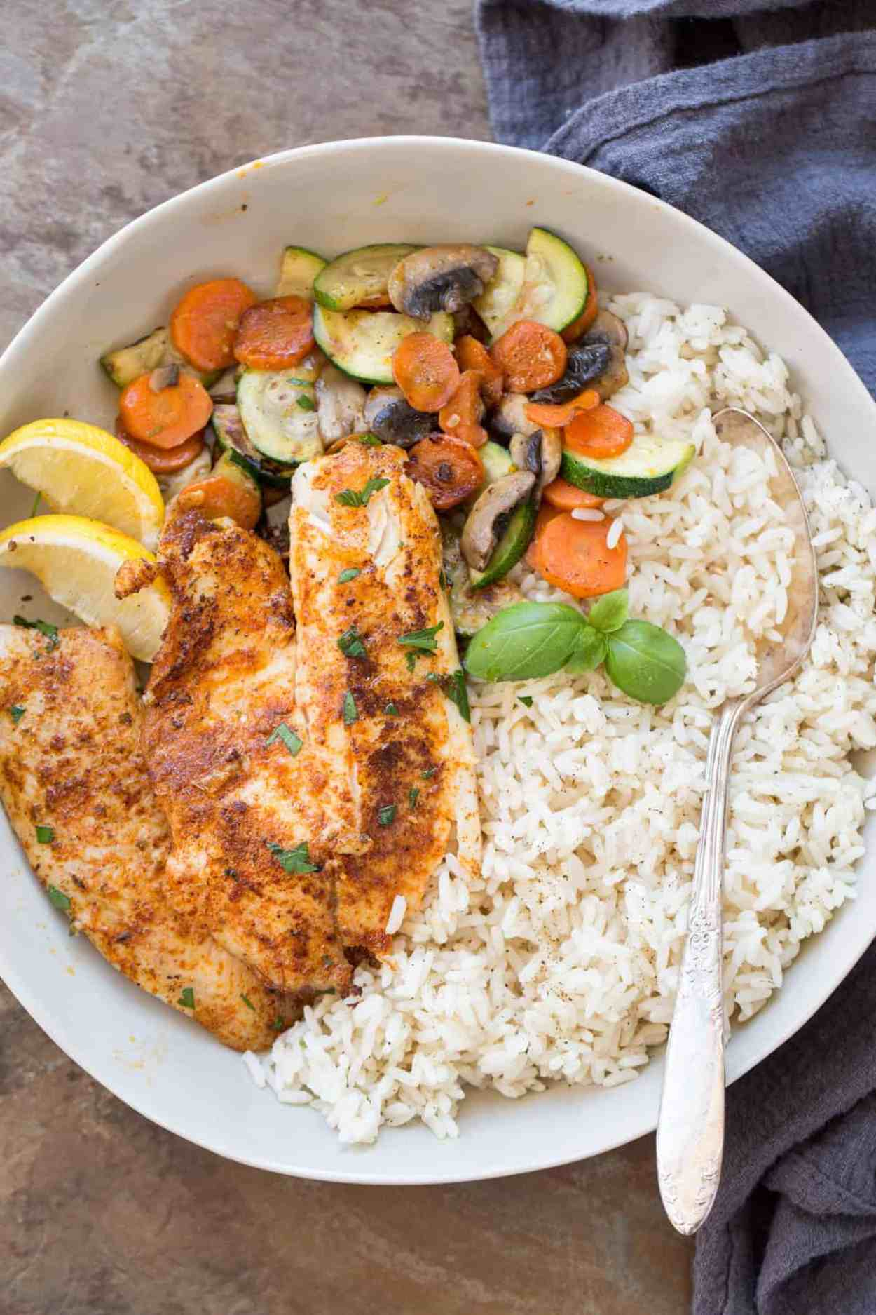 Tilapia fish on a plate with rice and sauteed vegetables.