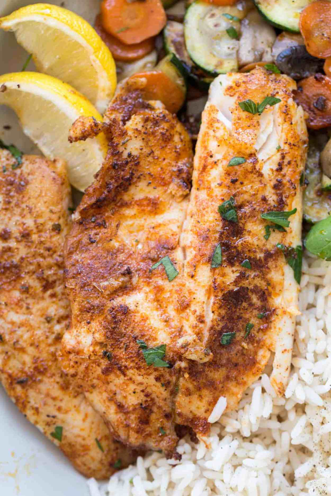Up close picture of blackened tilapia fish with fresh chopped herbs.