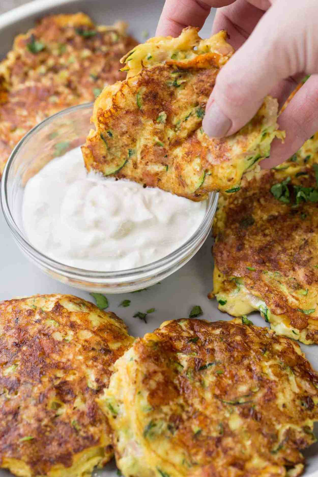 Zucchini Fritter dipped into the mayo mixture on a plate.
