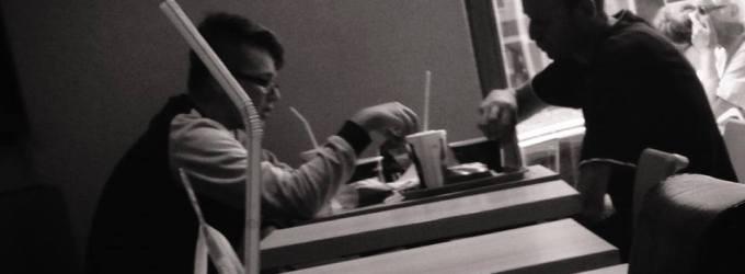 """Prima data a intrat baiatul in KFC, grabit, cu ochii iscoditori, cautand tabelele cu produsele si preturile afisate, tatal pasea in urma lui, preocupat sa inchida usa, sa salute agentul de paza, sa fereasca 2 studente care se grabeau spre usa... In timp ce baiatul deja s-a asezat la una din cozile existente, numarandu-si in pumn banii ce pareau """"la fix"""", tatal a ajuns in spatele lui si il intreba: - No bun, deci de care vrei? - Uite, e oferta aia cum ti-am zis, luam amandoi si iesim mai ieftin. - Bine, eu ma duc sa iau masa si astept, zise tatal si s-a asezat la 3 mese distanta de mine. Isi da jos din cap basca si curăță cu palma goală niște fărâmituri (imaginare?) de pe masă, în așteptarea copilului. Imi surprinde privirea scurt si, zambind familiar, ca si cum eram de ani de zile vecini de scara sau de gospodarie, ma salută neinteligibil. Zâmbesc înapoi si dau din cap a binețe. Cu cele 2 meniuri idendice cumparate, feciorul revine la masa, imparte egal continutul tavii cu tatal lui si apoi tatal spune ceva ce as vrea sa pot spune si eu de fiecare data cand ma voi pune la masa cu copiii mei: - Doamna ajuta! Isi fac amandoi semnul crucii si incep sa manance. E momentul in care am facut fotografia."""