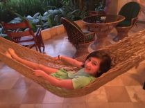 The outdoor patio had hammocks, a table with cushiony chairs and rocking chairs.