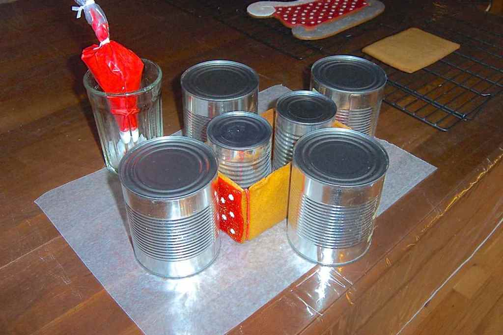 """Side view of the cans holding up and holding together the glued sides of the sleigh """"box"""" for drying."""