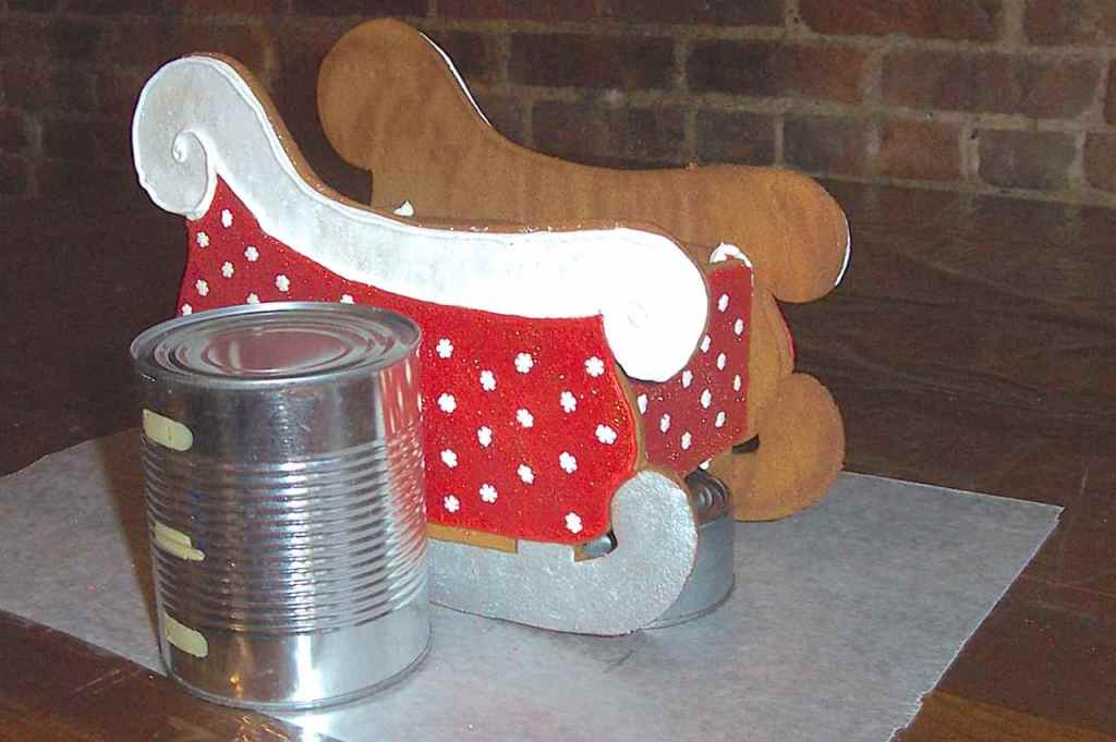 Side view of cans holding up cookie sleigh pieces while it dries.
