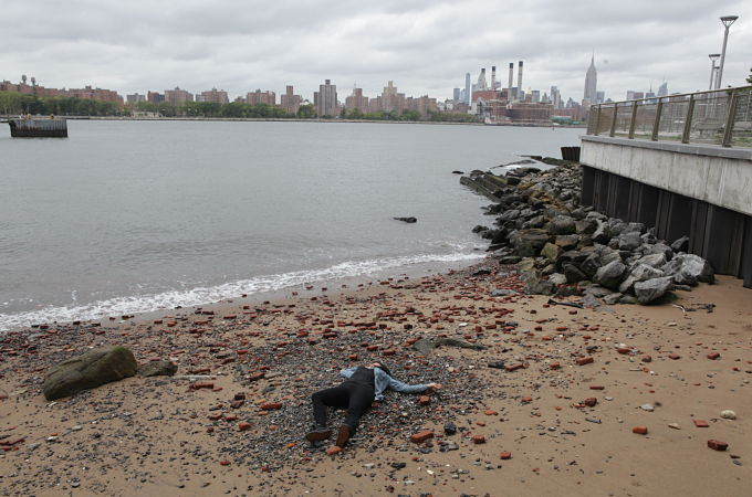 Beach scene from Pretty Dead with faux dead body and NYC in the background.