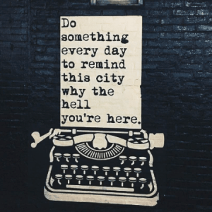 typewriter illustration against brick wall