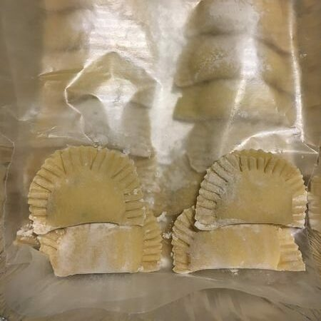 Mom's homemade - raw - on tray ravioli in two rows