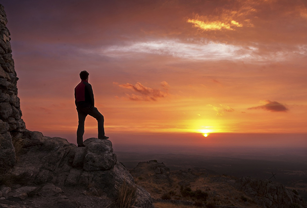 A man on a mountain staring at the sunrise.