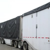 Two white chip truck trailers with a black trailer roll tarp on each one with one closed and one open.