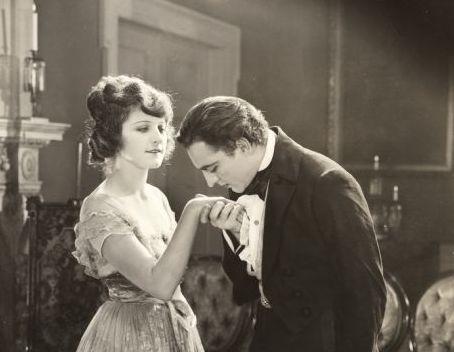 Mies suutelemassa naista kädelle.
