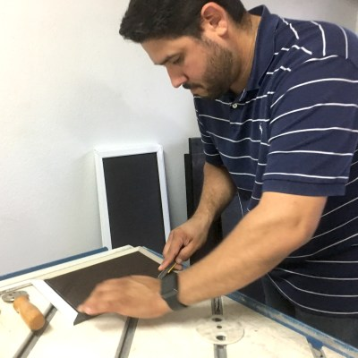 Rene Castro, owner of RRC Quality Solar Screens works on a custom-size solar screen for a client.