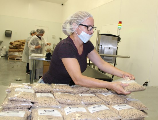 Romi Cordova, a veteran worker at Dipasa, arranges bags of roasted sesame seeds. (VBR)