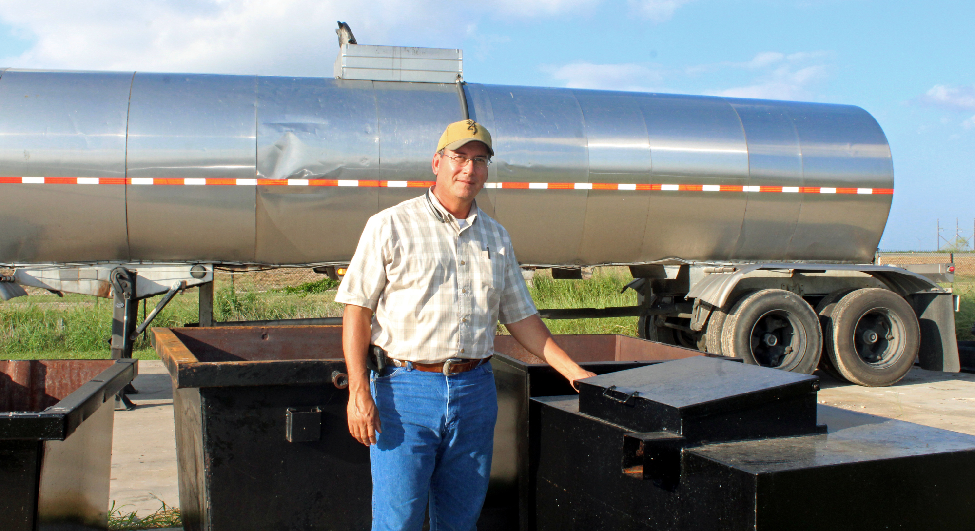Fatty Chem plant manager Hector Martinez stands in front of a company tanker truck and next to used cooking oil collection containers. (VBR)