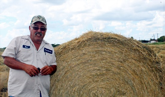 Max Ramirez with a round hay bale during a recent harvest on his land. (VBR)