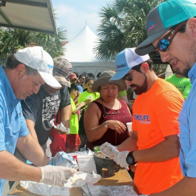 Noble's Rene Capistran and Alfredo Garcia, in light blue shirts, prepare tacos for the participants at a children's fishing tournament in Brownsville. Texas Noble Builders also served as sponsors for the event. (VBR)