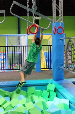 A boy hangs above a pit filled with foam squares to soften his fall. (VBR)