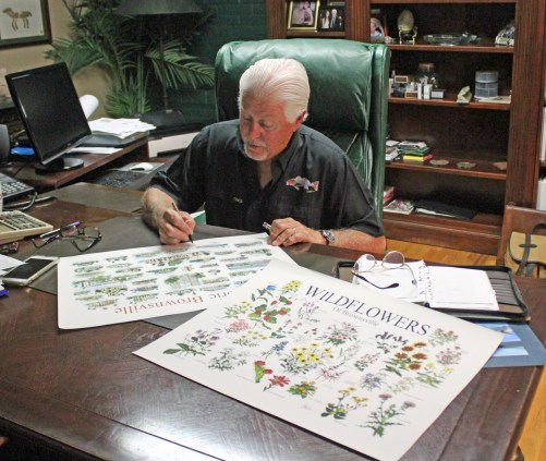 Don Breeden signs posters with images of his artwork detailing historic Brownsville and wildflowers. (VBR)