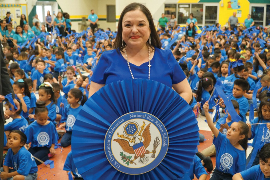 Sam Houston Elementary Principal Debra Thomas holds up a blue ribbon emblem as students celebrate in the background. Sam Houston is one of just 26 schools in the state to earn a national Blue Ribbon award.