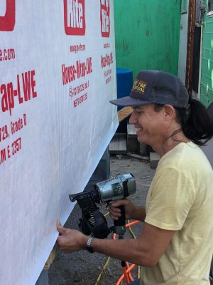A volunteer installs house wrap to prepare the house for siding installation. (Courtesy)