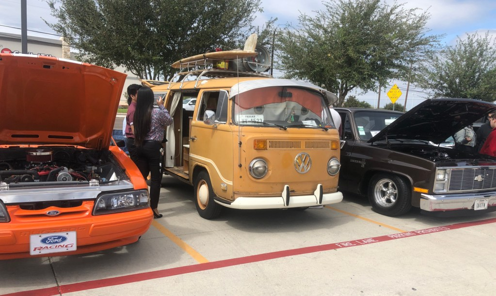 Visitors snap pictures of a VW Campmobile.