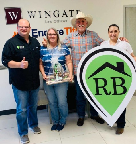Ryan Peterson with clients after the closing of the sale of their home.