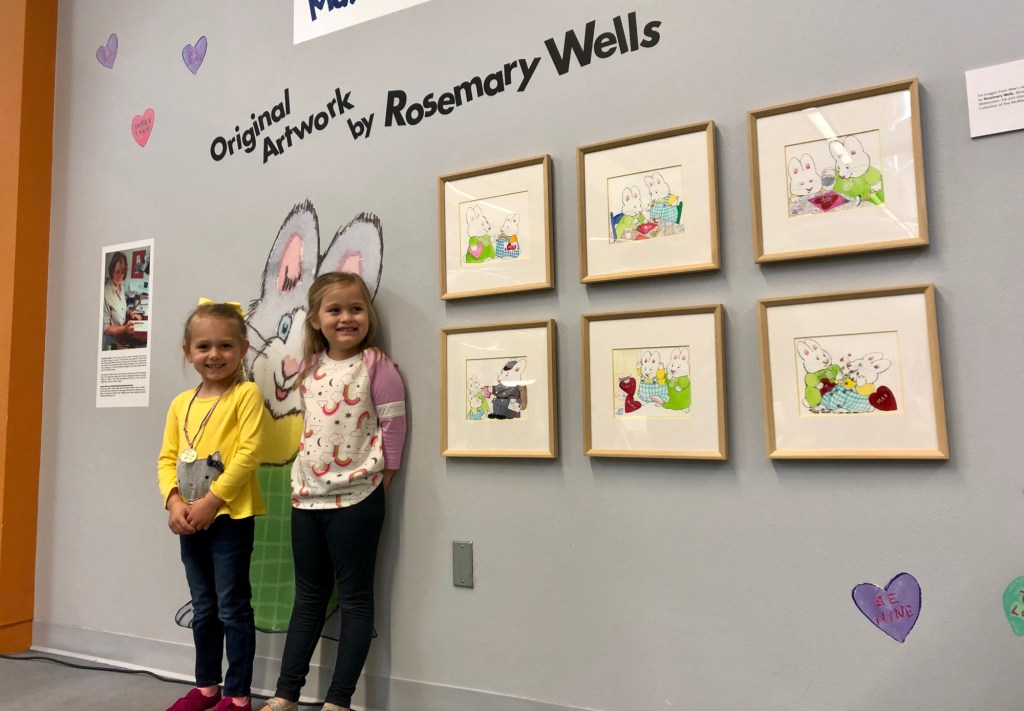 """Two girls admire the six original artworks from """"Max & Ruby."""""""