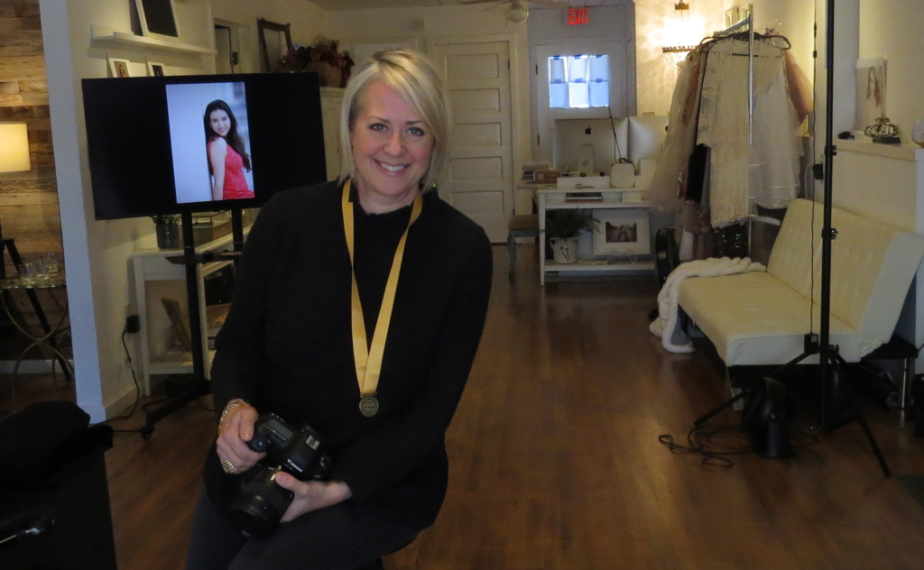 Nicole Gates proudly wears her Portrait-Masters-Associate-Level medal around her neck while in her studio.