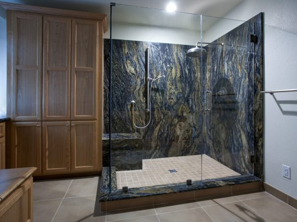 A shower with granite walls, a tile floor, and an overhead rain shower head.