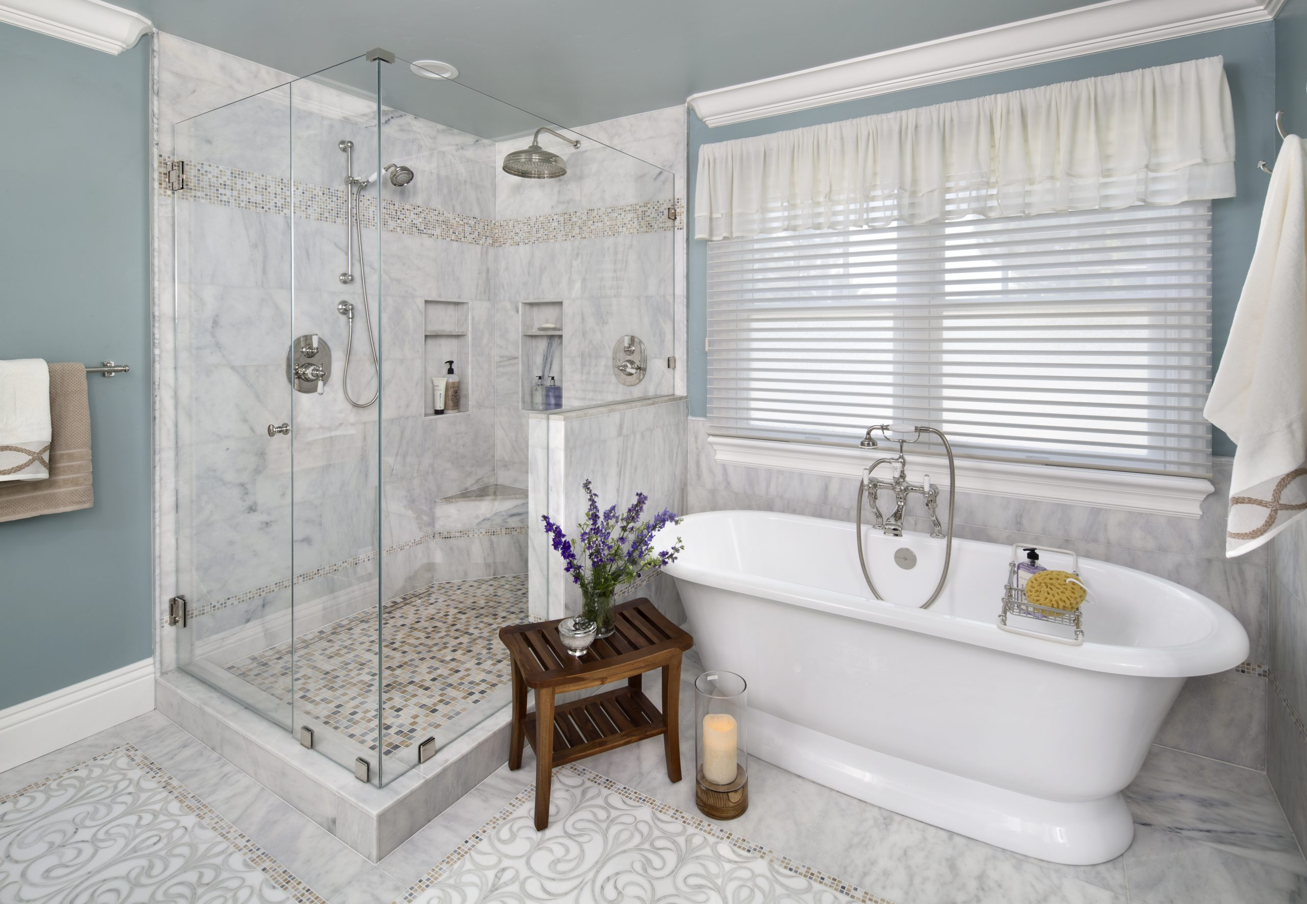 A white porcelain tub with a stone floor shower.