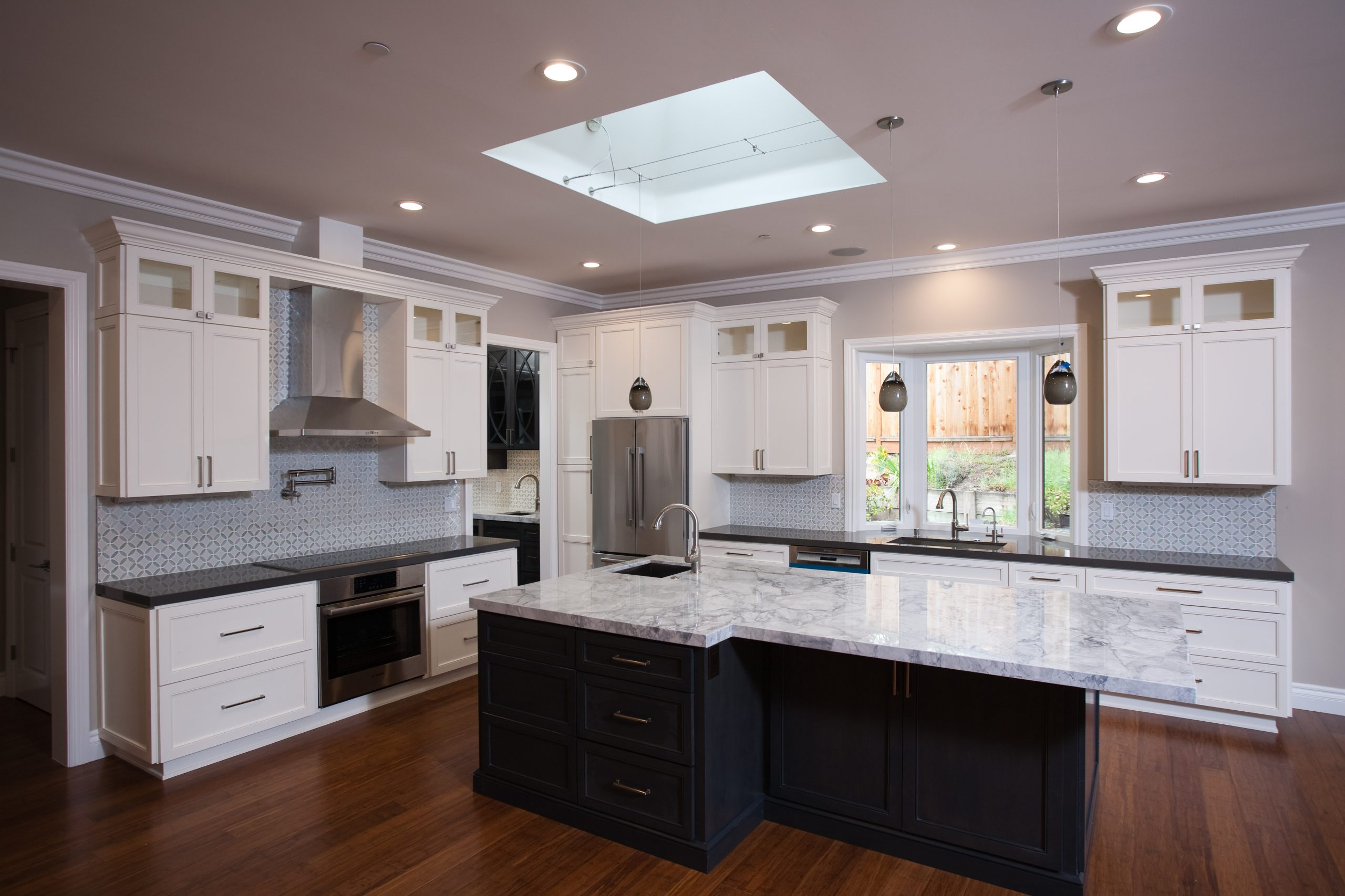 An updated kitchen with a large granite kitchen island and new steel appliances.