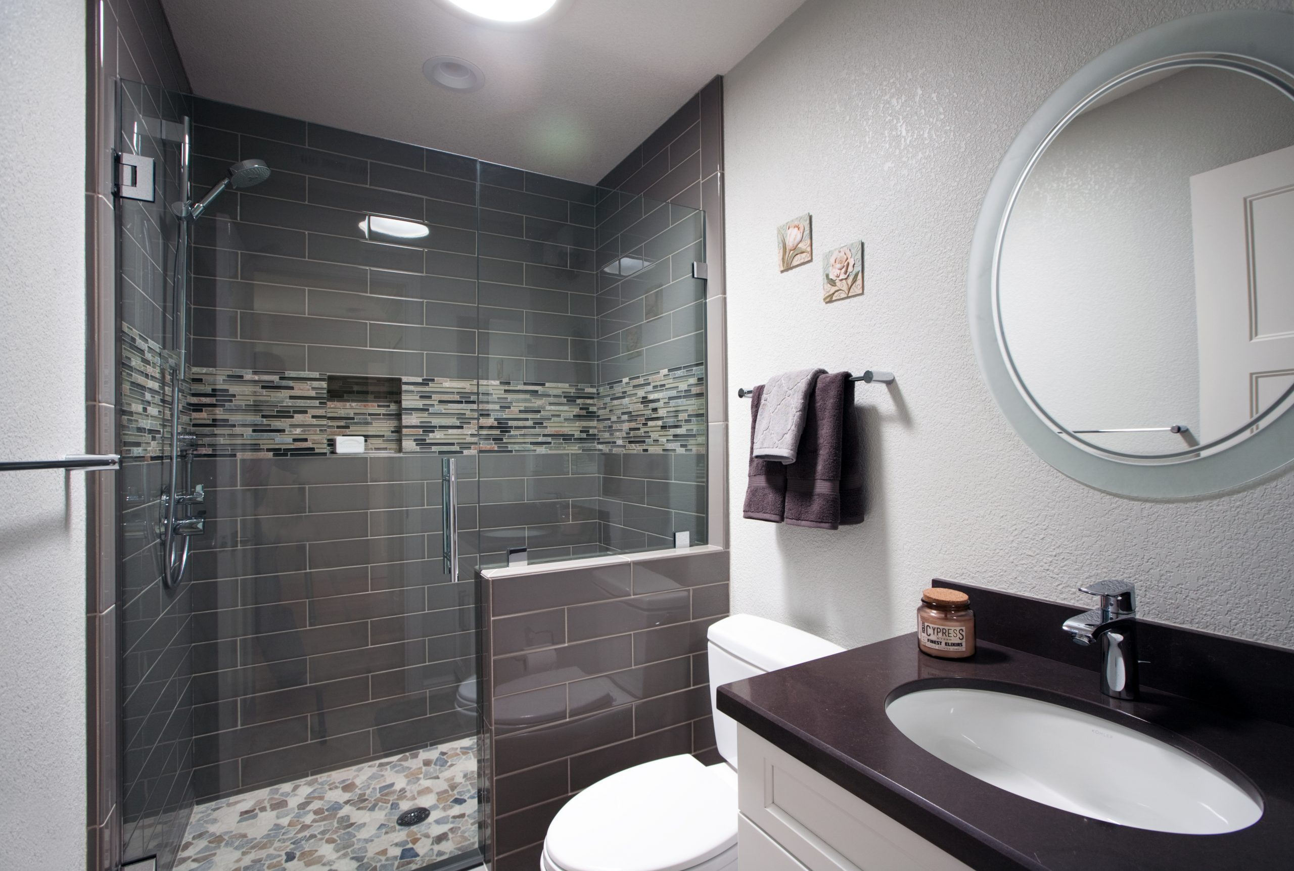 A modern bathroom with grey tile and stone shower floor.