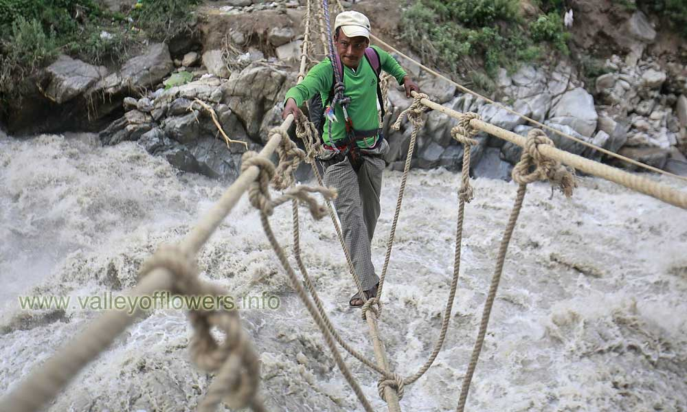 Man crossing Alaknanda river by rope bridge at Govindghat