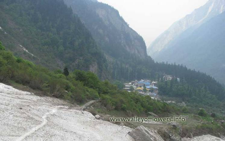 A frozen river and village Ghangaria in the month of June.