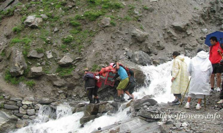 Porters taking a palanquin inside the valley of flowers, They are crossing a shallow stream near the entry gate of the valley.