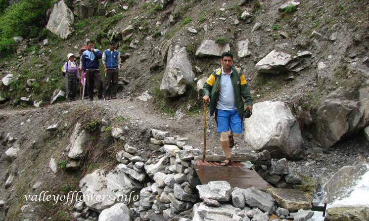 Devkant Sangwan crossing a stream near the entry gate of the valley
