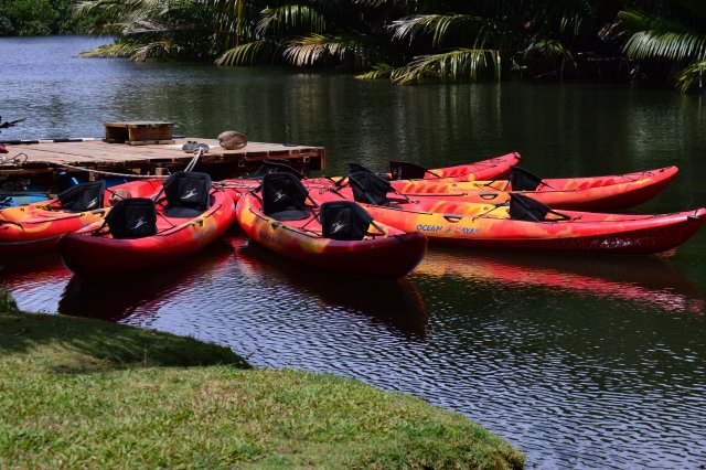 Kayaks awaiting adventure atop calm and beautiful Talofofo River waters.