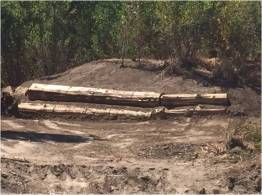Logs and boulders are used to stabilize creek banks.